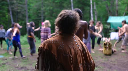divinity : Diverse people enjoy spiritual gathering People are seen enjoying playful dance during a multicultural retreat in woodland, mixed and colorful individuals experience native traditions together. Stock Footage