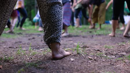 sanar : Diverse people enjoy spiritual gathering A closeup view on the bare feet of a woman wearing loose fitting leopard print pants during a meditative dance routine during a multicultural festival in nature