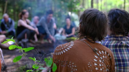 divinity : Diverse people enjoy spiritual gathering A close-up and rear view of a woman wearing a native style shawl, sitting by a smoking campfire in woodland with a group of people celebrating spirituality. Stock Footage