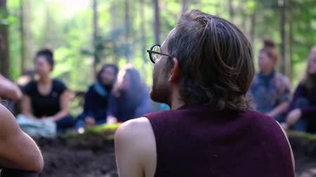 divinity : Diverse people enjoy spiritual gathering Slow motion footage of a slim caucasian man, wearing glasses and sleeveless top, sitting by a smoldering campfire during a shamanic retreat in nature.