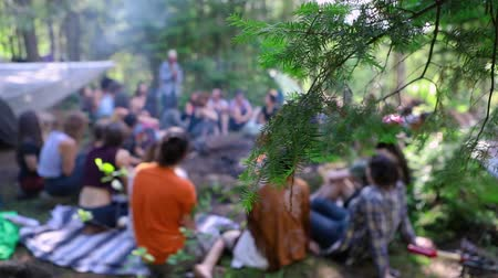 悟り : Diverse people enjoy spiritual gathering A large group of people are seen in slow motion, blurred behind tree branches, as they come together in nature seeking mindfulness and enlightenment.