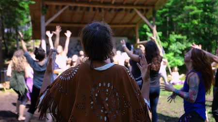 divinity : Diverse people enjoy spiritual gathering A woman wearing native style loose shoulder clothing is seen in slow motion from the back, as a group of people experience sacred barefooted dance in nature.