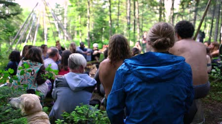 divinity : Diverse people enjoy spiritual gathering A curious dog turns head to the side as a multiethnic group of people celebrate freedom and spirituality together in a woodland campsite, short slow-mo video.