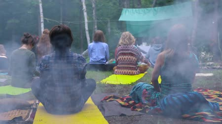 divinity : Diverse people enjoy spiritual gathering Campfire smoke sets a calm & mysterious atmosphere as a mixed group of people experience deep prayer & meditation during a woodland retreat for body & mind. Stock Footage