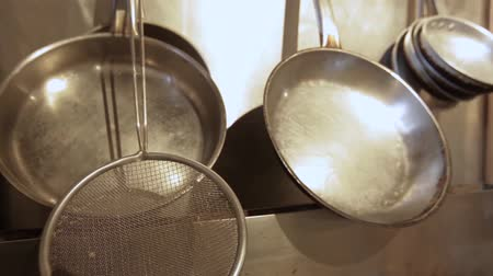 kitchenware : Silver cooking implements are shot close-up inside an eatery, hanging over an industrial oven. Hospitality and catering concept.