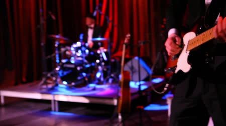 staging : Camera pans round a stage inside a music bar as a country and blues group perform a set. Details of a man playing an electric guitar and singers by mic stands. Stock Footage