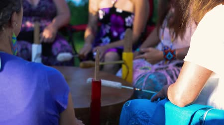 nativo americano : An intergenerational mix of people are seen close-up in slow-mo, playing a traditional large powwow drum during a shamanic celebration in a singing circle. Stock Footage