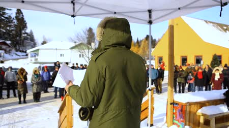 rali : An over the shoulder view of an environmentalist giving a speech on climate change during a demonstration in a snowy town. Onlookers are seen in the background.