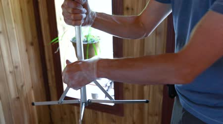 rothadás : Closeup footage of an indoor environmental quality (IEQ) assessor at work, setting up a stainless steel impactor on a tripod inside a residential property.