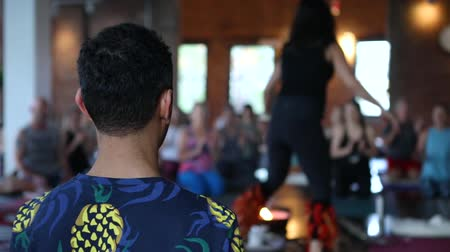 View from behind a young male with dark hair inside a popular health and wellness class. A blurry instructor is seen with a spiritual drum in the background.