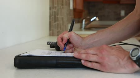 iaq : Closeup and slow motion of footage on the hands of a man filling in a form during an indoor environmental quality (IEQ) inspection, checking building standards.