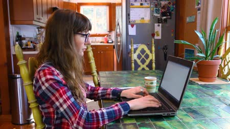 Girl with glasses wearing a checkered shirt is typing on her keyboard. Fixed wide angle scene