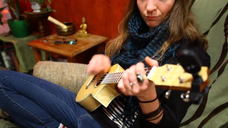 Close up of a young girl learning how to play ukulele sitting in a sofa in her living room - traveling up