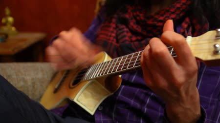 гитара : Close up of guitarist with long hair wearing red scarf and purple shirt, playing ukulele sitting in a sofa in his living room - traveling up Стоковые видеозаписи