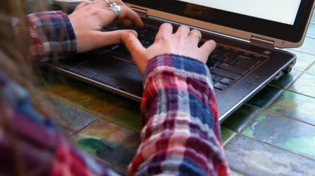 authenticity : Girl wearing a checkered shirt is typing on her black laptop keyboard. Travelling up closeup from the back Stock Footage