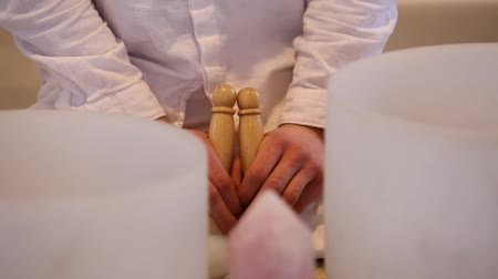 esotérico : Traveling up on a man dressed in white, singing and holding the wood sticks used for the crystal bowls, close up on his hands, front view