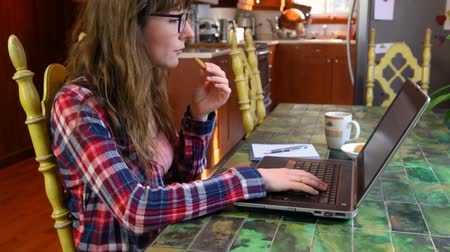 authenticity : Girl wearing a checkered shirt eating a cooking while watching something on her black laptop computer. Travelling up wide angle from the side Stock Footage