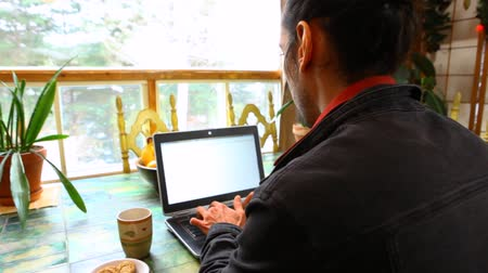 esquerda : Young man wearing a black jacket is typing on his black laptop with cookies and coffee by his side. Panning left, closeup