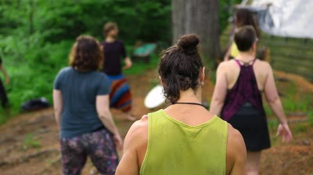 istenség : A slim muscular bohemian man with hair tied up and green vest is seen from behind, as people experience playful and sacred dance during a multicultural retreat.