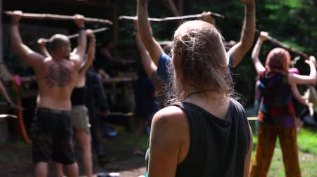 short clip : A short slow motion clip of a mixed group of individuals seeking mindfulness and enlightenment during a shamanic festival in a forest camping site. Stock Footage