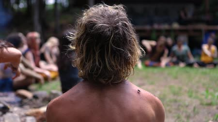 A closeup and rear view of a young shirtless man, sitting around a camp fire with a mixed group of people as they practice playful dance and meditation.