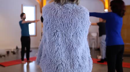 coaching : Fixed angle of the back of a woman wearing a furry vest, doing exercise as part of a yoga class, with blurry people in a circle doing the same in the background Stock Footage