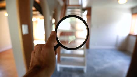 denetleme : First person perspective during a residential home inspection, using a magnifying glass to take a closer look around the empty family room with open plan stairs