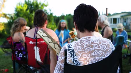 native american culture : An over the shoulder view of a woman playing a native drum as a gathering of multigenerational people come together to play mystical music.