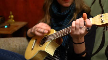 fauteuil : Close up of a young girls hands learning how to play ukulele sitting in a sofa in her living room - panning right