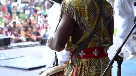 cerimonial : A close up and rear view of a drummer playing a traditional percussion instrument and wearing colorful African clothes during a cultural music concert. Vídeos