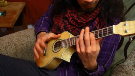 Close up of guitarist with long hair wearing red scarf and purple shirt, playing ukulele sitting in a sofa in his living room - panning right