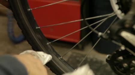 Closeup footage of a cycle repairman cleaning the inner wheel and spokes of a pedal bike inside a garage. Stock Footage