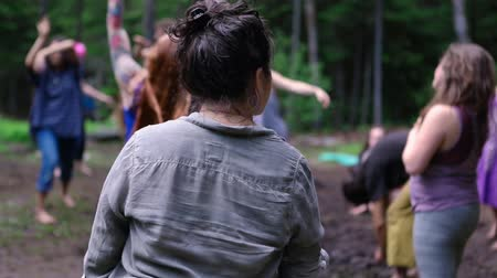 shaman : A young woman wearing grey shirt with short black hair is seen from the rear, experiencing free shamanic dance used to balance chakra and reach tranquility. Stock Footage
