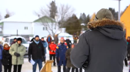 rewolucja : An environmentalist is shot from behind giving a speech about climate change as the camera pans round to show blurry ecological activists in the background.