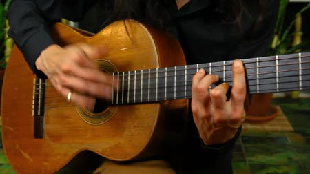 tablao flamenco : Panning right on a professional guitarist with long hair practicing rasgueado or rasguedo flamenco strumming techniques at home Archivo de Video