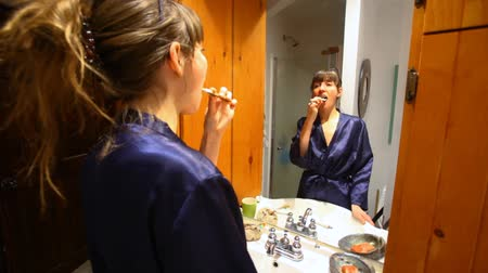 preventive : Young woman is looking at her reflection in the bathroom mirror and brushing her teeth - traveling up, focus in the mirror