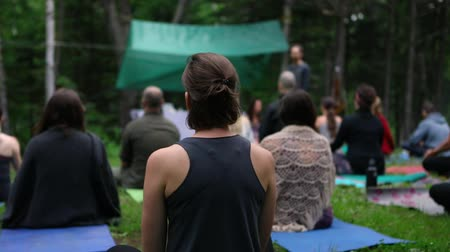 divinity : A young slim woman with hair tied up is viewed from behind during a forest retreat celebrating mindfulness and enlightenment, slow motion footage.