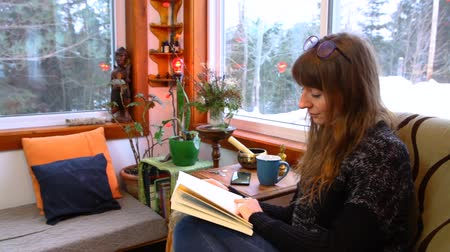 Young woman with wooly grey shirt and glasses is reading a book surrounded by windows. Panning right wide angle