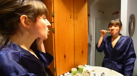 escova de dentes : Young woman is looking at her reflection in the bathroom mirror and brushing her teeth - fixed angle, switch focus Stock Footage