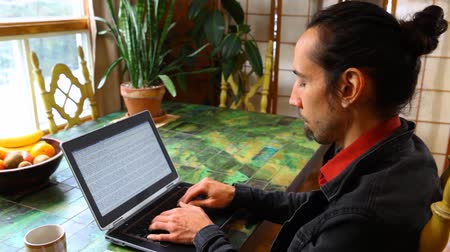 Young man wearing a black jacket and a red shirt is typing on a black laptop in his dining room. Panning left Stock Footage