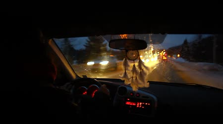 colgantes : Young man is driving through his small city at night. Dream catcher in the car. Fixed angle shaky scene from the back Archivo de Video