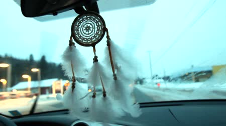 Driving in the winter with the wipers on, while a white dream catcher bounces around the middle of the car. Fixed angle scene