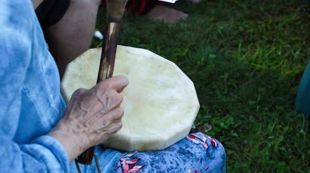 An older and mature woman is seen experiencing shamanic and indigenous culture during a pow-wow gathering at a local park, playing a small handicraft drum.