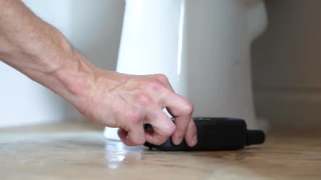 iaq : Closeup footage of an environmental quality inspector using a small digital device around the base of a ceramic toilet pan during a domestic living assessment.