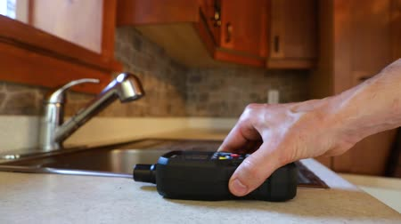 iaq : Closeup footage of a man using an electronic device to detect for signs of mold and harmful spores in a residential kitchen during an environmental quality test. Stock Footage