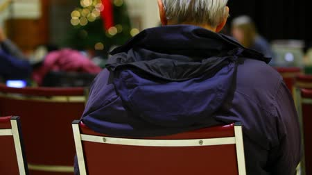 origens : wearing a winter coat, sitting on a chair and listening to an official speech with blurry background seen from behind - traveling up