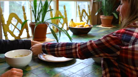Young couple are finishing their toast and soup meal on a green ceramic table by the window, they leave. Fixed angle closeup Stock Footage