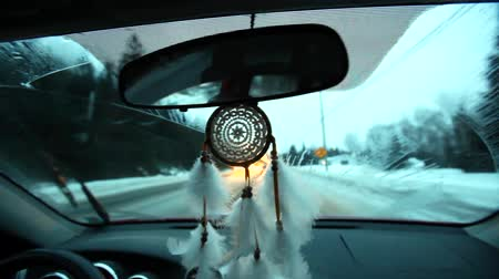 indios nativos : Driving in the winter with the wipers on, while a white dream catcher bounces around the middle of the car. Fixed wide angle scene Archivo de Video