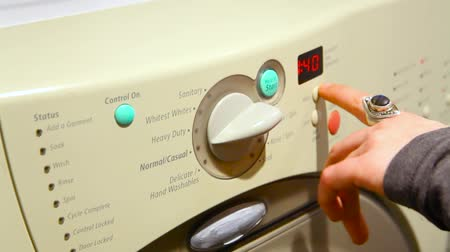 prát : Close up of girls hand pressing buttons and starting the washing machine in the utility room - fixed angle