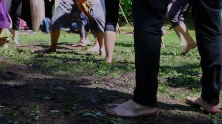 Slow motion camera panning footage at ground level as a mixed group of barefooted people dance and enjoy freedom on a grassy woodland clearing.